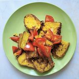 crostini gialli del pane fritto con i pomodori su un piatto verde su un fondo bianco fotografie stock