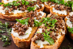 Crostini with goat cheese and Beluga lentils Royalty Free Stock Images