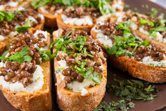 Crostini with goat cheese and Beluga lentils Stock Photo