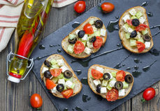 Crostini grec de style avec du feta, les tomates, le concombre, les olives et les herbes images libres de droits