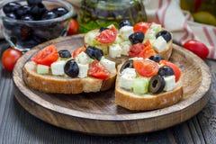 Crostini grego do estilo com queijo de feta, tomates, pepino, azeitonas, ervas imagem de stock