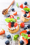 Crostini with grilled baguette, cream cheese and berries Stock Photo