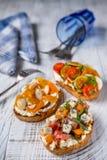 Crostini italiano com o tomate do queijo na madeira branca fotos de stock