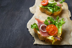 Crostini italiano dei antipasti con il prosciutto, l'insalata ed il pomodoro immagine stock