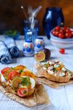 Crostini italien avec la tomate de fromage sur le bois blanc image stock