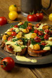 Crostini with prosciutto, swiss chard, cherry tomato vinaigrette Stock Image