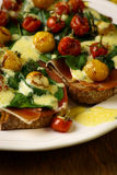 Crostini with prosciutto, swiss chard, cherry tomato vinaigrette Stock Images