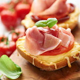 Crostini with prosciutto on wooden board Stock Photography