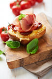 Crostini with prosciutto on wooden board Royalty Free Stock Photo