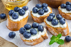 Crostini with ricotta cheese, blueberries and honey Stock Photo