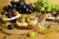 Crostini with roasted grapes, goat cheese, walnuts, honey Royalty Free Stock Image