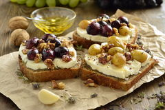 Crostini with roasted grapes, goat cheese, walnuts, honey Stock Photo