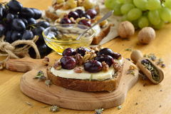 Crostini with roasted grapes, goat cheese, walnuts, honey Royalty Free Stock Photo