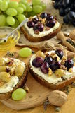 Crostini with roasted grapes, goat cheese, walnuts and honey Stock Photos