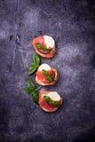 Crostini with salmon, mozarella, tomato and basil stock photos