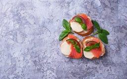 Crostini with salmon, mozarella, tomato and basil royalty free stock images