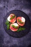 Crostini with salmon, mozarella, tomato and basil stock photography