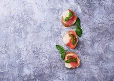 Crostini with salmon, mozarella, tomato and basil royalty free stock photography