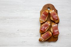 Crostini with serrano ham and chutney on rustic wooden board, top view. White wooden background. stock images
