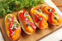 Crostini. Crostini, small toasts with colored peppers and spices on a wooden board Stock Photography