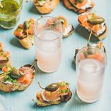 Crostini with smoked salmon and pink grapefruit cocktails, square crop Stock Images