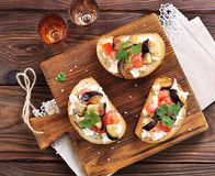 Crostini with soft cheese, eggplant, tomatoes and garlic. Royalty Free Stock Photography