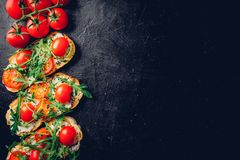 Crostini with toasted baguette, cottage cheese and fresh organic cherry tomatoes. Old black textured background. Italian food. Top. View image. Copyspace for royalty free stock photos