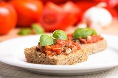 Crostini with tomato. Garlic and basil. National italian dish Royalty Free Stock Photos