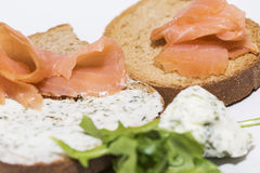 Crostinis with smoked salmon and Cheese. Toast with herb cheese, salmon and rocket royalty free stock photo