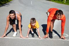 Crouch start. Family of runners standing at the start line in a crouch start position Royalty Free Stock Photography