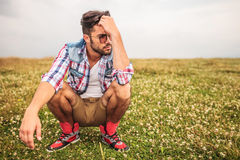 Crouched casual man in a grass field thinking Royalty Free Stock Photo