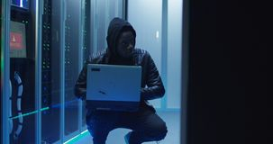 Crouched hacker in a data center. Medium shot of a hacker in a hoodie on laptop in corporate data center with rows of working rack servers royalty free stock images