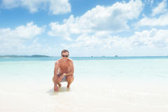 Crouched man in swim suit and sunglasses Royalty Free Stock Image