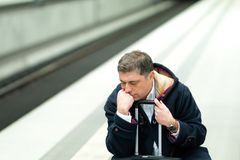 Crouched man waiting for the train. Tired and demoralised traveler waiting for his delayed train Stock Photos