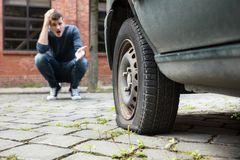 Crouched Man Pointing At Punctured Car Tire. Crouched Worried Young Man With Hand On Head Pointing At Punctured Car Tire royalty free stock image