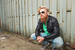 Crouched young bearded man Stock Image