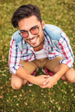 Crouched young man in a grass field Stock Photo