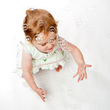 Crouching 2 Year Old Girl Catching Bubbles Stock Photography