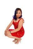 Crouching Asian woman. Royalty Free Stock Photos