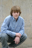 Crouching boy. Brown haired young teen boy crouching by cement wall Stock Photos