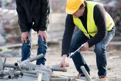 Crouching civil engineer examining metal tubes. On construction site Stock Images