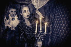Crouching in the dark. Bloodthirsty male vampire in medieval dress creeps up a young beautiful lady. Halloween. Black-and-white photo Royalty Free Stock Photo