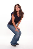 Crouching girl. Isolated shot of a brunette crouching to listen Royalty Free Stock Photography