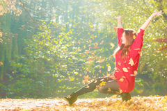 Crouching girl in autumnal forest. Royalty Free Stock Photo