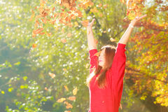 Crouching girl in autumnal forest. Royalty Free Stock Photography