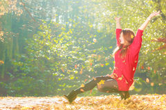 Crouching girl in autumnal forest. Stock Photos