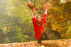 Crouching girl in autumnal forest. Royalty Free Stock Image