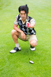 Crouching golfer holding club looking away Royalty Free Stock Photo