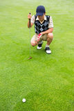 Crouching golfer looking at the ball stock photo