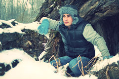 Crouching handsome young man in winter. Fashion portrait of a crouching handsome young man looking at something in winter in front of big old tree trunk Stock Photography